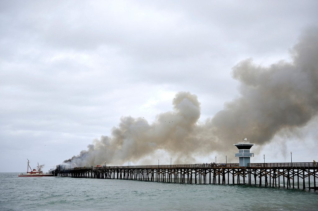 Firefighters work to put out a fire at the end of the Seal Beach Pier on Friday morning.  The fire damaged the pier and destroyed the former site of Ruby's restaurant which closed in 2013.  ///ADDITIONAL INFORMATION: Slug: sealbeachpier.fire.0520.jag, Day: Friday, May 20, 2016 (5/20/16), Time: 7:33:15 AM, Location:  Seal Beach, California - Seal Beach Pier Fire - JEFF GRITCHEN, STAFF PHOTOGRAPHER